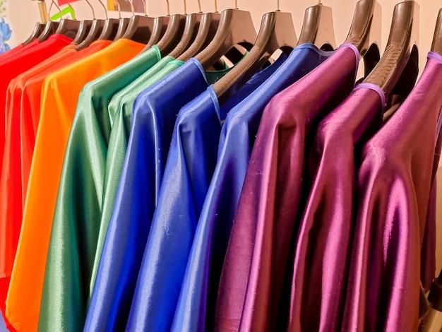 Couleurs arc-en-ciel. choix de vêtements décontractés sur cintres noirs, isolés sur blanc.variété de robes en soie sur cintres.vêtements colorés suspendus dans une armoire