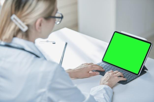 Couleurs-un bouton sur l'écran de la tablette, une vue par-dessus l'épaule d'un travailleur médical
