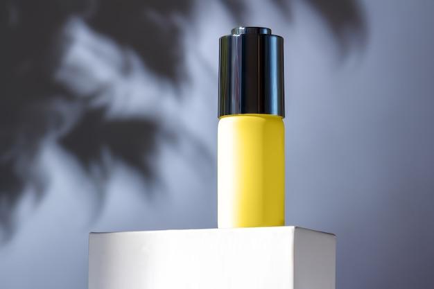 Couleurs grises et illuminatrices à la mode 2021 ans. composition élégante avec un flacon compte-gouttes jaune sur un support sur un mur gris avec l'ombre des feuilles.