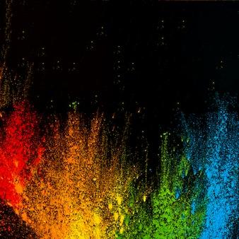 Couleurs holi multicolores de style arc-en-ciel disposées sur un fond noir