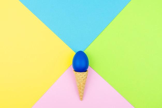 Couleurs pop. fond multicolore festif avec des paillettes de sucre brillantes dispersées sur du papier, cône de gaufrette et oeuf de pâques.