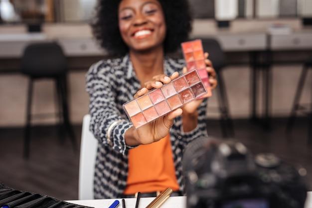 Couleurs vives. beau modèle à la peau foncée avec des cheveux bouclés souriant tout en démontrant une nouvelle palette de couleurs