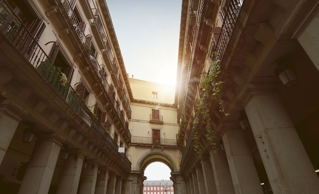 Couloir entre les anciens bâtiments avec arcade au soleil