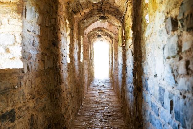 Couloir sombre dans le donjon avec lumière à la fin