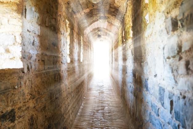 Couloir sombre dans le donjon avec des rayons de soleil à la fin