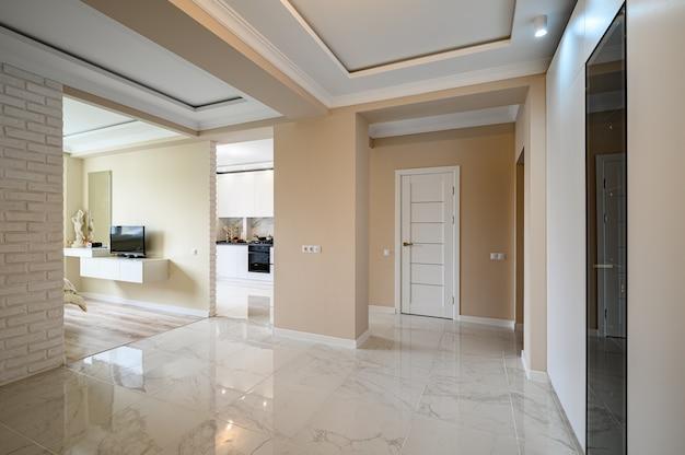 Couloir vide de studio moderne avec cuisine blanche et chambre beige