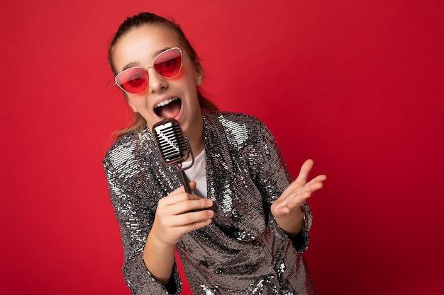 Coup d'une adolescente brune heureuse et positive émotionnelle portant une veste élégante et brillante