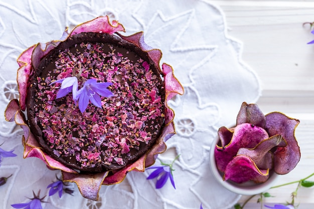 Coup d'angle supérieur d'un gâteau violet végétalien cru poire avec des poires déshydratées sur une table blanche