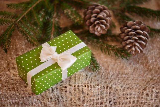 Coup de cadeau de noël emballé et pommes de pin
