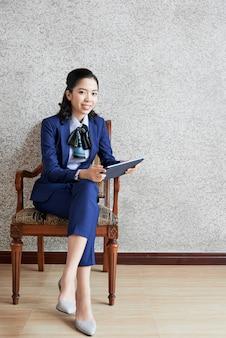 Coup complet de femme élégante gaie avec tablette numérique assis dans un fauteuil et regardant la caméra