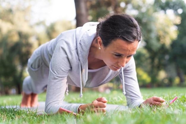 Coup complet femme faisant des planches dans la nature