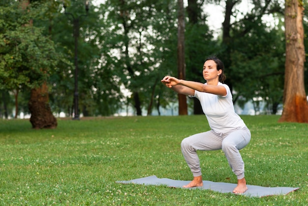 Coup complet femme faisant des squats sur un tapis de yoga