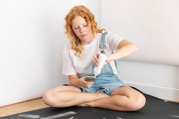 Coup complet femme versant de la peinture sur un pinceau