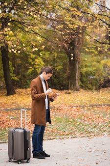 Coup complet jeune homme avec des bagages dans le parc