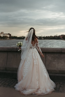 Coup de corps complet vertical d'une mariée portant une robe blanche et une robe de mariée debout sur un pont