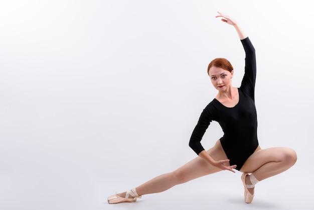 Coup de corps entier de femme danseuse de ballet posant sur le sol isolé sur fond blanc