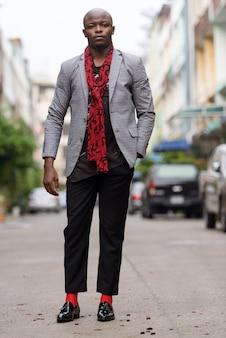 Coup de corps entier de jeune homme d'affaires africain chauve avec écharpe à l'extérieur