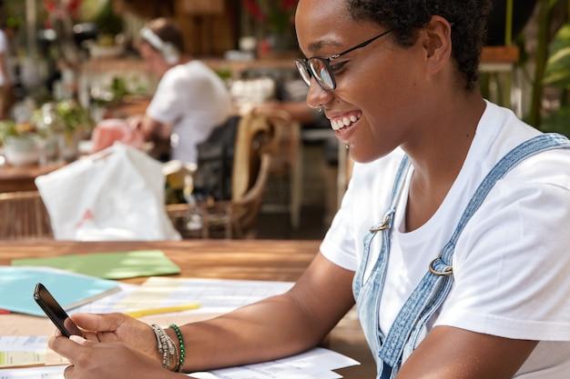Coup de côté d'une fille hipster joyeuse vêtue d'un t-shirt blanc décontracté