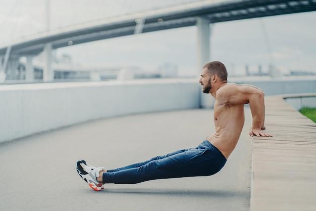 Coup de côté d'un homme musclé fait des exercices de poussée inversée pour former les bras