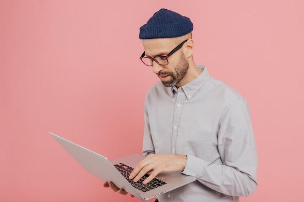 Coup sur le côté d'un homme séduisant se tient devant un ordinateur portable ouvert, fonctionne dans l'internet