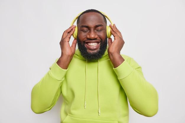 Coup de demi-longueur d'un beau mec barbu gai à la peau foncée écoute de la musique dans des écouteurs sans fil sourit à pleines dents a des dents blanches parfaites porte un sweat-shirt vert isolé sur un mur blanc