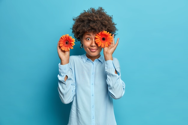 Coup de demi-longueur d'heureuse jeune femme aux cheveux bouclés couvre les yeux avec des gerberas orange aime les fleurs a la bonne humeur porte une chemise isolée sur un mur bleu