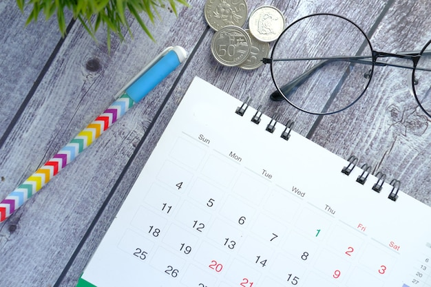 Coup de détail d'un calendrier et d'un stylo sur un bureau en bois