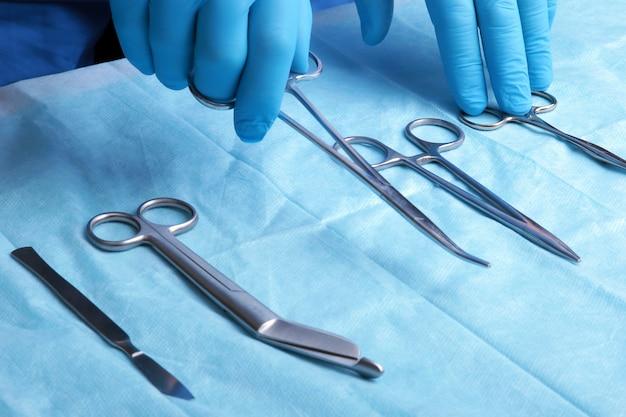 Coup de détail d'instruments de chirurgie stérilisés avec une main saisissant un outil