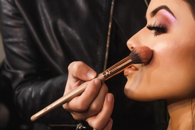 Coup de détail d'une maquilleuse colorant les joues d'une belle jeune fille dans le salon de beauté.
