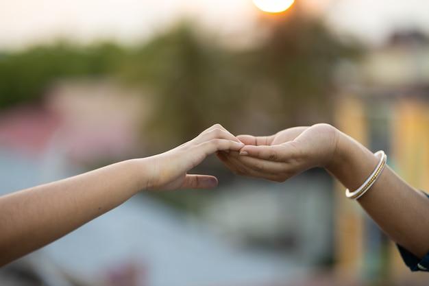 Coup de focus peu profond de deux mains se touchant doucement