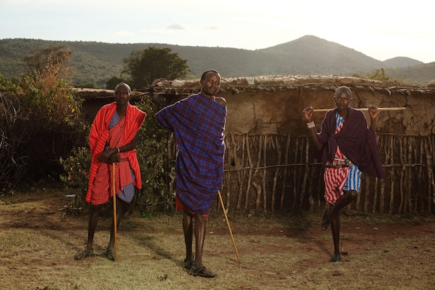 Coup de focus peu profond de trois hommes africains tenant des bâtons