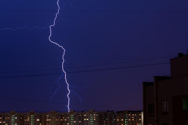 Coup de foudre dans la ville de moscou, en russie. la foudre dans la ville du soir au-dessus des bâtiments résidentiels. ciel bleu foncé.