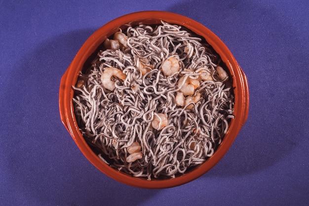 Coup de frais généraux d'une assiette d'anguille aux crevettes sur fond bleu