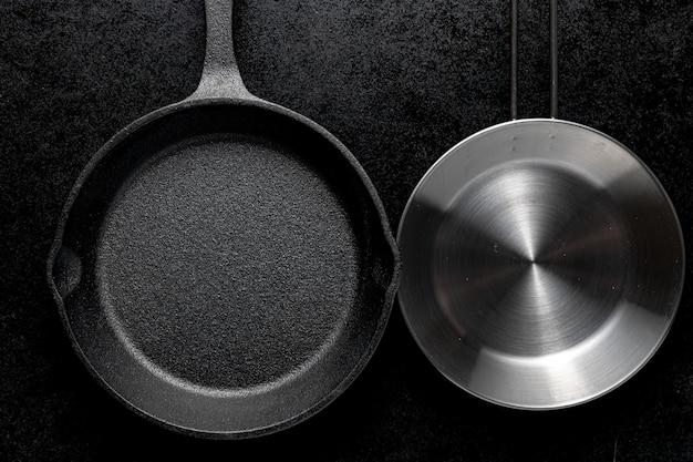 Coup de frais généraux de deux poêles à frire en métal sur fond noir