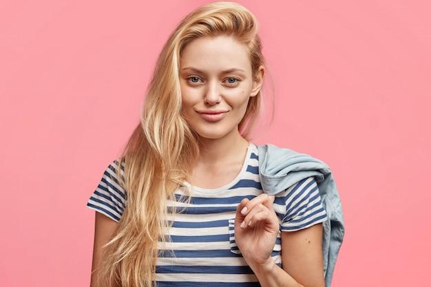 Coup franc de bonne belle jeune femme avec du maquillage, habillé en t-shirt marin, détient une veste en jean, regarde avec une expression joyeuse confiante