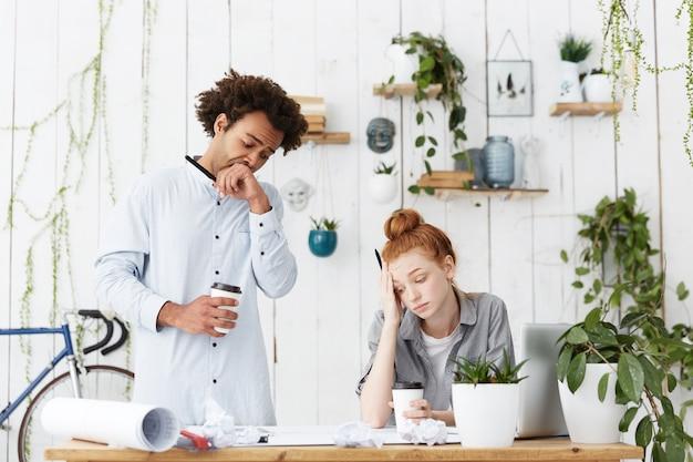 Coup franc de deux jeunes architectes homme et femme fatigués et endormis face à la date limite
