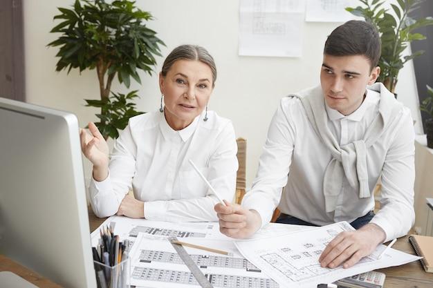 Coup franc de l'élégante femme architecte senior aux cheveux gris, montrant un écran d'ordinateur, expliquant le point de vue à son jeune collègue masculin tout en travaillant sur un nouveau projet de logement ensemble,