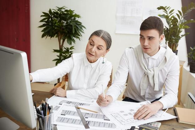 Coup franc d'une femme mature attrayante développant un projet de construction dans un bureau léger, travaillant avec son jeune collègue, à l'aide d'un système de cao sur un ordinateur générique, pointant sur l'écran