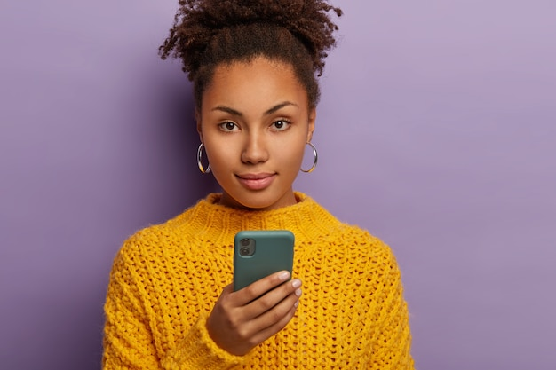 Coup franc d'une femme sérieuse du millénaire aux cheveux noirs bouclés, utilise un téléphone portable, regarde directement la caméra, porte des vêtements jaunes