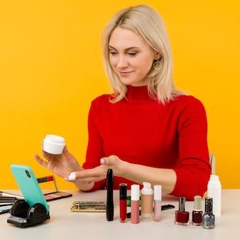Coup franc d'une jolie jeune blogueuse caucasienne présentant des produits de beauté et diffusant une vidéo en direct sur un réseau social, montrant une crème anti-âge tout en enregistrant un tutoriel de maquillage