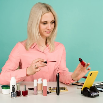 Coup franc d'une jolie jeune femme de race blanche blogueuse présentant des produits de beauté et diffusant une vidéo en direct sur un réseau social, en utilisant un brillant à lèvres lors de l'enregistrement d'un tutoriel de maquillage