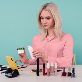 Coup franc d'une jolie jeune femme de race blanche blogueuse présentant des produits de beauté et diffusant une vidéo en direct sur un réseau social