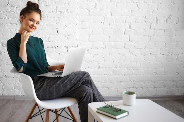 Coup franc de joyeuse belle jeune pigiste caucasienne utilisant un ordinateur portable générique pour un travail lointain, assis avec désinvolture dans une chaise à une table basse avec une tasse, un livre et des lunettes. les gens et la technologie