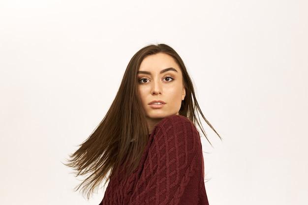 Coup horizontal de belle fille avec une longue coiffure droite et une peau claire ayant excité le regard surpris, posant en studio, le vent jouant avec ses cheveux