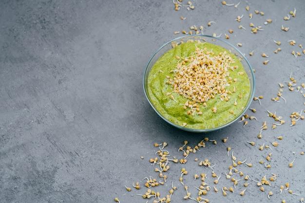 Coup horizontal du bol en verre avec smoothie vert végétarien frais contenant beaucoup de vitamines