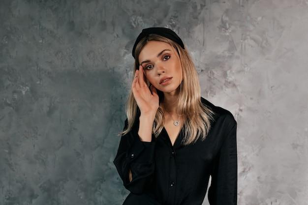 Coup intérieur de belle femme en noir posant à la caméra