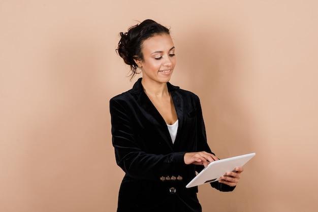 Un coup isolé d'une femme d'affaires noire heureuse en studio, ordinateur portable, smartphone