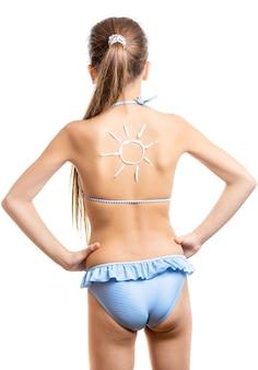 Coup isolé d'une jolie fille avec du soleil sur le dos dessiné par une lotion solaire