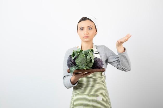 Coup de jeune cuisinier tenant une assiette de chou et de brocoli sur blanc