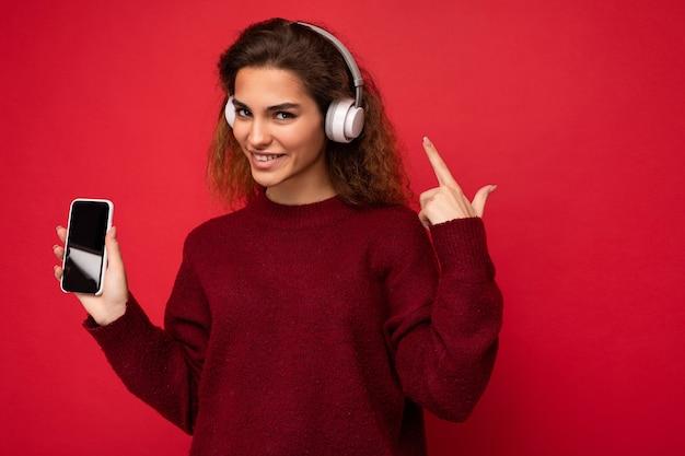 Coup de jolie jeune femme brune frisée positive portant un pull rouge foncé isolé sur rouge